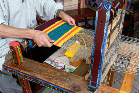 Hands of man weaving fabric on a wooden loom. Traditional Russian folk art. Carpet weaving process.