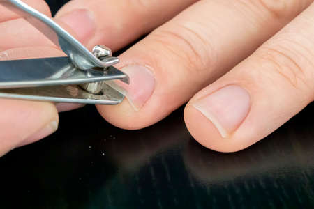 hand manicure with nail clipper. close up over black background. self-cutting nails. close-up nail cutting