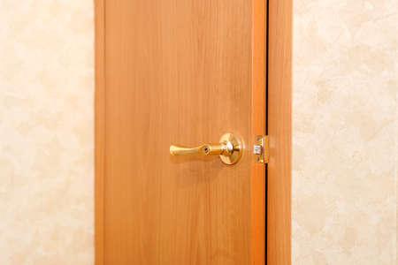 Hotel room or apartment doorway with open door. door handle close-up