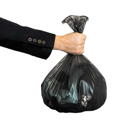a black garbage bag in a man's hand is isolated on a white background. 免版税图像