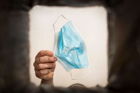 man's hand throws protective medical or surgical mask into the trash outdoors. Protection against influenza and the viral ncov epidemic, quarantine, concept image.