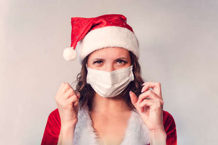 Beautiful young woman in red Santa Claus costume and protective medical mask against virus. Concept of celebrating Christmas in covid 19 pandemic and quarantine. Mrs. Santa angry and sick