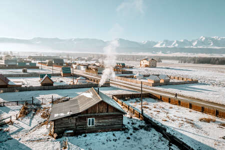 Russian village. Wooden huts with smoke from chimneys in the winter season