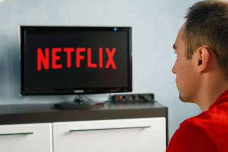 A young man watches Netflix on his TV and at home. TV remote in the foreground, blurred background on the TV. Editorial