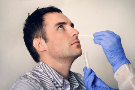 doctor taking nasal mucus test sample from male nose performing respiratory virus testing procedure. Checking the nasal cavity in ENT. PCR polymerase chain reaction Banco de Imagens