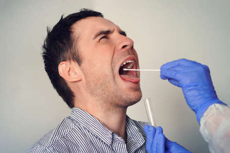 Doctor Doing Coronavirus Test For male Patient. DNA test. Collection of mucus from the throat for research in the laboratory. Taking a saliva sample from a man. PCR polymerase chain reaction