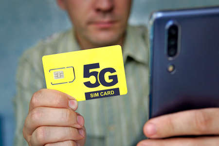 man holds a yellow SIM card with the inscription 5G and a mobile phone in his hand. Replacing the SIM card and switching to high-speed Internet. Banco de Imagens