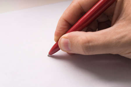 A mans hand writes with a red pen on a white paper surface. Top view of female hand with pencil on blank paper sheet. On cardboard background Banco de Imagens