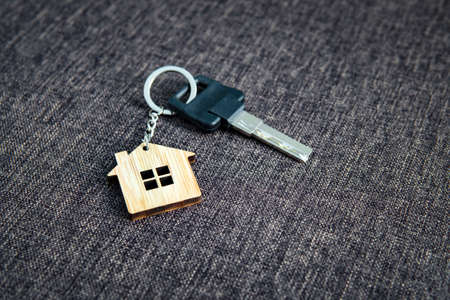Close up of key with house-shaped key ring at dark sackcloth background. Concept of purchasing living apartment. Being at home. House key lying on the flooring. Becoming an owner of house. Keychain.