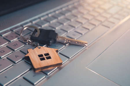 Mortgage concept with keys and house-shaped key ring on laptop keyboard. Find dream house in internet concept. Online assistance in searching dwelling. Close up of key lying on computer keyboard.