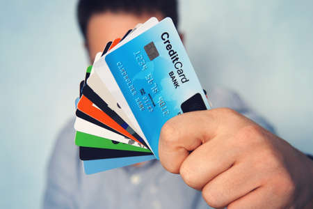 Young man in light blue shirt showing many types of credit cards. Businessman in casual wear holding in hand various payment cards. Stack of cards with biometric scanner card on the top. Banking