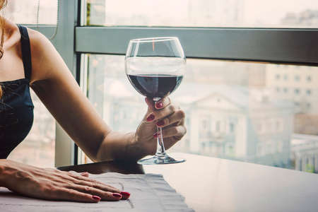 A young woman which her hand holding with glass red wine as a looking out on the window. Banco de Imagens