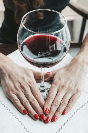 Woman in red holding wine glass. Banco de Imagens