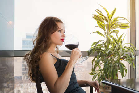 A young beautiful girl in a black dress sits in a restaurant and drinks wine from a glass.