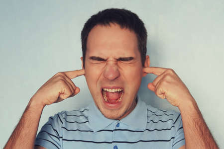 Stressed frustrated young man plugging his ears with fingers and keeping eyes closed while having headache