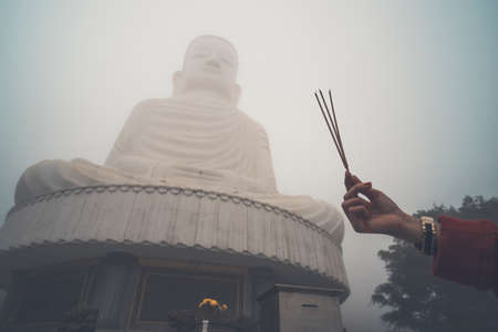 Buddha image with incense. Three incense sticks in a woman's hand against a big Buddha in the fog. Bana hill. Vietnam. Danang.