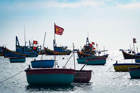 traditional Vietnamese round boat on the sea with a red flag on it.