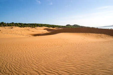 Big red dune on the background of blue sky. Phan Thiet, Vietnam.