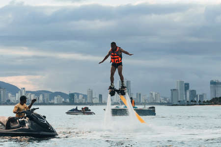 VINPEARL RESORT, NHA TRANG, VIETNAM - 05.01.2019: The new spectacular sport, the flyboard is showed in the coast of beach on the sunset. Man on flyboard. 新聞圖片