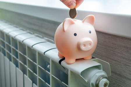 The concept of paying for heating in homes with a cold climate. piggy bank pig on a white metal radiator. The concept of saving on utilities 版權商用圖片