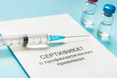 A document for recording vaccinations made in Russia, a syringe and a bottle of vaccine on a blue background. Translated from Russian: Certificate of preventive vaccinations.