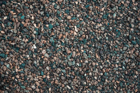 Gravel texture. Small stones, little rocks, pebbles in many shades of gray, white, brown, yellow color. Background of small stones in oval shape. Texture of little rocks