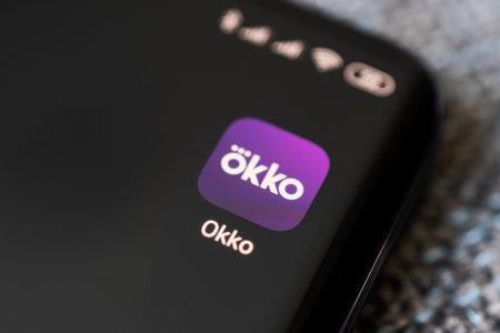 Okko - Russian multimedia service, online cinema. app on smartphone. April 3, 2021 Barnaul, Russia Редакционное