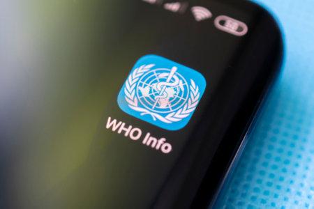 The World Health Organization app for information on a black smartphone screen. April 3, 2021 Barnaul, Russia Редакционное