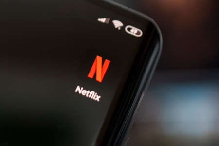 Close-up of cell phone with netflix logo on screen. Netflix is an international leading subscription service for watching TV episodes and movies. April 3, 2021 Barnaul, Russia