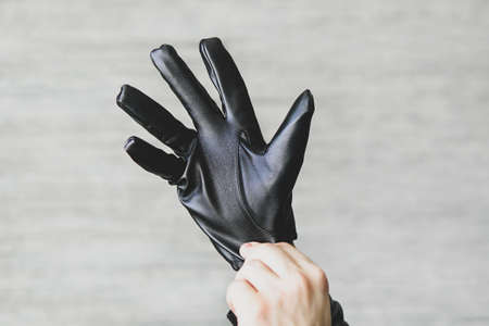 A man puts black leather gloves on his hands on a gray background. leatherette gloves