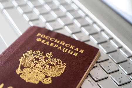 Passport of the Russian Federation on a gray laptop keyboard. Identification of the user on the Internet. Prohibition of access to the Internet without passport data.