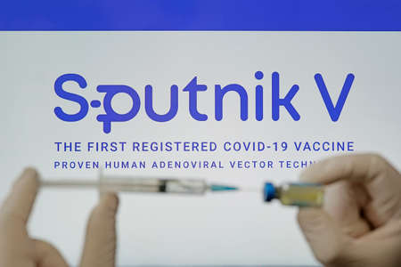 A doctor prepares a vaccine against the coronavirus covid 19 on the background of the Sputnik V logo. January 18, 2021, Barnaul, Russia. 新闻类图片