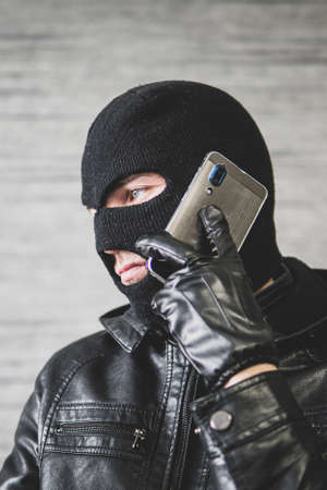 Young adult in black clothes with hidden face. Ill-intended fraudster uses mobile. Fraudster calls. Mobile racket. Hacker hijacks by phone. Cellphone account fraud. Scam