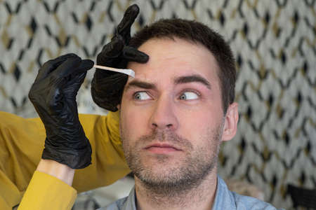 Beautician plucking beautiful bearded man eyebrows with tweezers in beauty salon. Female hands plucking eyebrow tweezers to relaxed bearded brutal man.