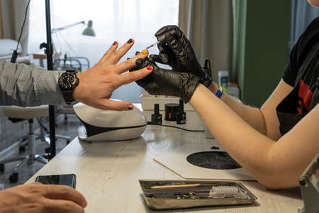 Professional nail care concept. Close-up of manicurist hands at work. A man gets a manicure. Coloring of men's nails. Design of male manicure.