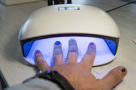man using UV light dryer. Manicure, spa salon concept. Beauty and fashion. a man's hand dries painted nails under an ultraviolet lamp 스톡 콘텐츠