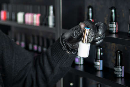Set of different nail varnishes on shelves in cosmetic store. choose the color of nail polish. the manicurist opens a bottle of nail polish. a bottle of nail polish in a woman's hand. 스톡 콘텐츠