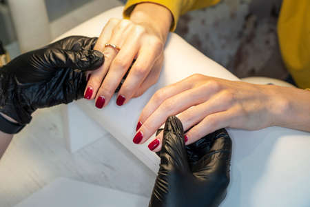 The manicurist holds hands of the client in beauty salon. manicure in the salon