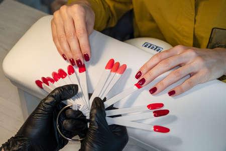 Gel polish. Nail polish in different colors. Woman at nail studio chosing color of nail polish.