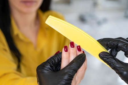 Beauty industry concept. Woman manicurist master in gloves is polishing client's nails using file. Portrait of working young female in cosmetology salon, clinic. Hygiene and care for hands. 스톡 콘텐츠