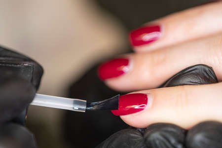 manicurists paints her nails painted. Woman manicurist master in gloves is polishing client's nails using file. working young female in cosmetology salon, clinic.