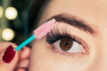 Mascara Applying. Long Lashes closeup. Mascara Brush. Eyelashes extensions. Makeup for black Eyes. Eye Make up Apply, Eyebrows shaping. Beautiful woman eyes make-up