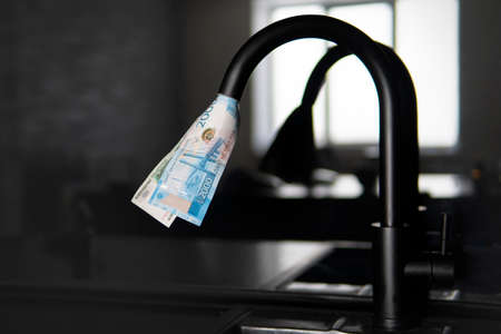 water tap spewing american dollar bills. Expensive water supply. The concept of increasing the price of public utilities for the population. Expensive hot and cold water at home.
