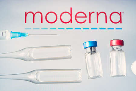glass ampoule with a clear liquid with the logo of a pharmaceutical company moderna on a blue background. March 13, 2021, Barnaul, Russia.