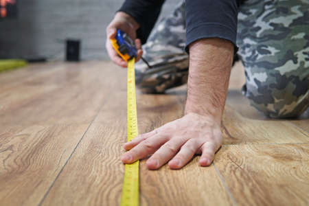repair, building and home concept - close up of male hands measuring wood flooring. laying laminate flooring. Measurement of the area of the apartment. 版權商用圖片
