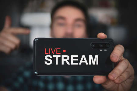 Handsome man making video blog. Focus on smartphone. young video blogger shoots content for his video blog on a social network. Live broadcast via the Internet. Concept