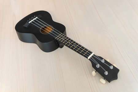 Guitar on textured wood. Acoustic guitar on wooden table with text space. Instrument of folk music. classic black concert ukulele 版權商用圖片