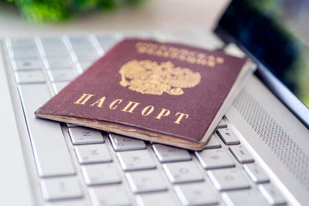 Passport of the Russian Federation on a gray laptop keyboard. Identification of the user on the Internet. Prohibition of access to the Internet without passport data. issuing a passport via Internet