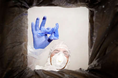 man in a protective suit throws used medical glove into a trash can. Bottom view from the trash can. The problem of recycling and pollution of the planet with garbage.