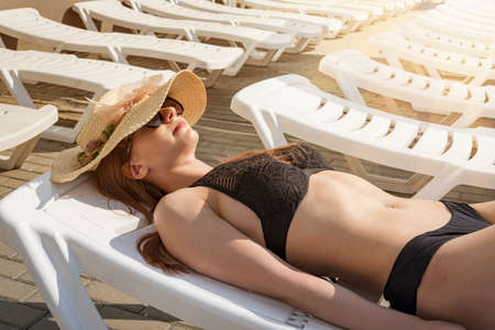 Beautiful young woman on sun lounger near swimming pool against the background of white sun loungers and bright sunlight